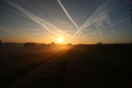 Sunrise with colored aircraft trails, fog on the meadows at River Hollandsche Ijssel in the Netherlands at nieuwerkerk. Stock Photo - 115996969