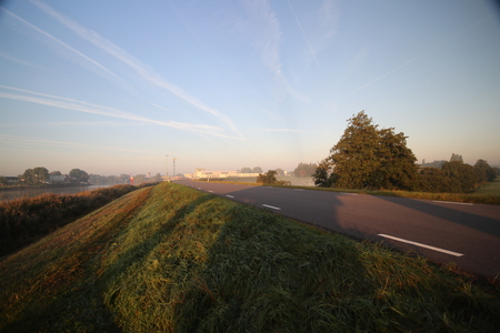 Sunrise with colored aircraft trails, fog on the meadows at River Hollandsche IJssel in the Netherlands at nieuwerkerk.