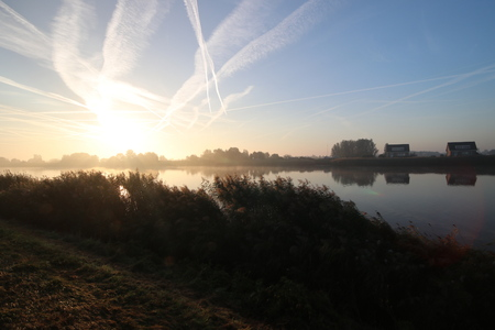 Sunrise with colored aircraft trails, fog on the meadows and dyke at River Hollandsche IJssel in the Netherlands at nieuwerkerk. Stock Photo