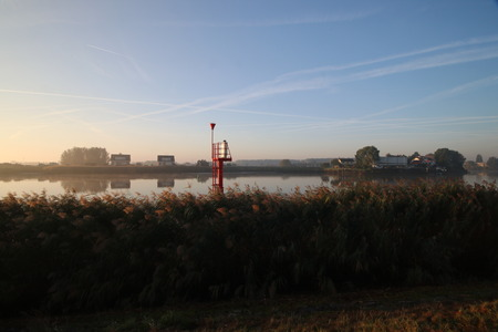 Sunrise with colored aircraft trails, fog on the meadows and dyke at River Hollandsche IJssel in the Netherlands at nieuwerkerk. Stock Photo - 119494867