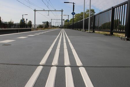 Guiding lines on platform for blind people to feel the save direction on station Lansingerland Zoetermeer in the Netherlands 版權商用圖片