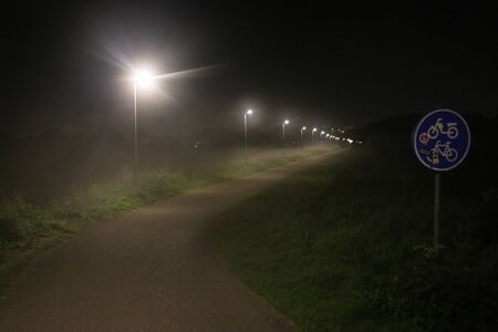 Street lights in the fog at the small bicycle lane between Capelle en Nieuwerkerk aan den IJssel