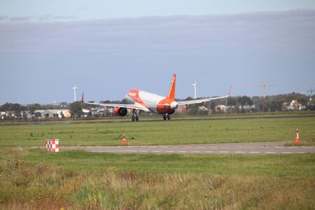 Aircraft ready for take-off at the polder runway strip at Amsterdam Airport Schiphol in the Netherlands type G-UZHV easyJet Airbus A320