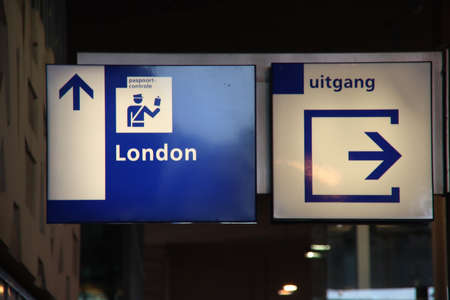 Blue and white direction sign to the passport control to london at Rotterdam station for Eurostar Editorial