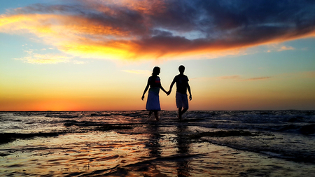Young couple walking on the beach in the waves