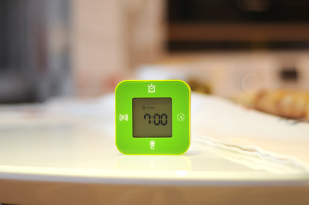 Green cube alarm clocks on the table on the blurred background