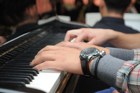Man's hands with wrist watches plays the piano Stock Photo