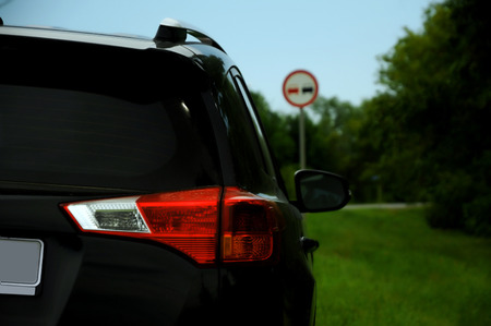 Black car on the roadside and sign on the background