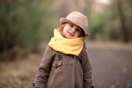 Little cute baby girl is walking, smiling, playing in autumn park outdoor nature yellow plants trees
