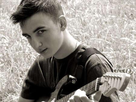 Young boy playing an electric guitar in a field. Zdjęcie Seryjne
