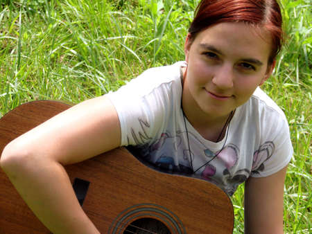 Young girl playing a western guitar in a field.