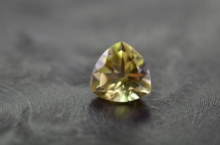 trillion: A shiny trillion shaped gem stone isolated on a black background