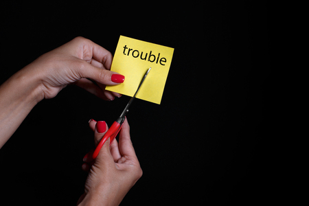 Photo on a dark background. Yellow sticker. Steel scissors. Word trouble.