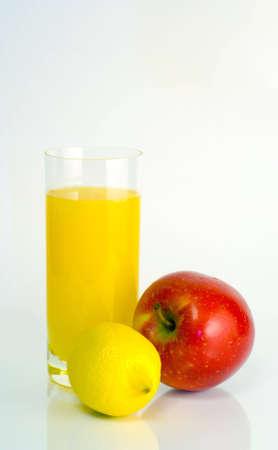Glass of orange juice, lemon and apple on white background