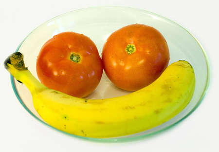 Banana and two red tomamos on glass plate on white background