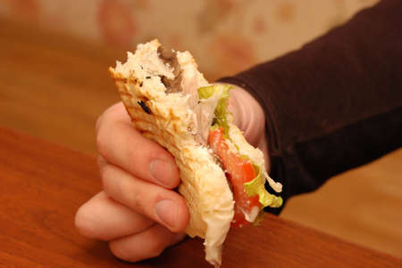 Male hand holding tasty delicious burger eating