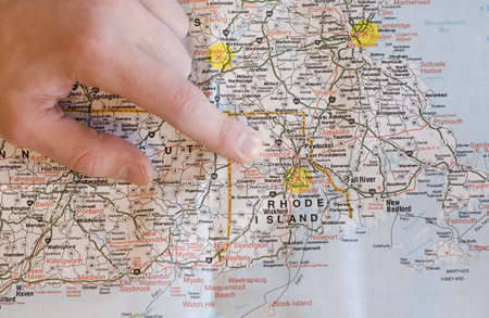 USA New England map with mans hand pointing to Rhode Island