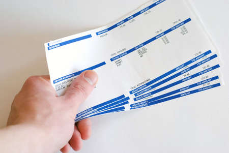 Male hand holding pay cheques checks in his hand on white background Stock Photo