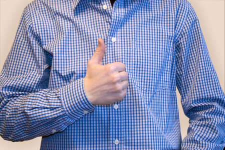 Approving sign with thumb by man in blue shirt