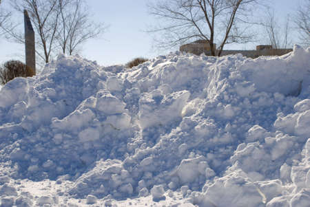 Winter snowscape of big snowdrifts and trees in city Stock Photo