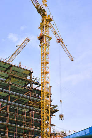 Building and yellow construction crane with sky on background