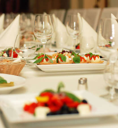 Table in luxury restaurant with white dishes and wine glasses