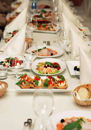 Table in restaurant with food silverware dishes and glasses