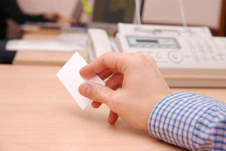 Man in blue shirt giving visit card to nobody telephone and office on background