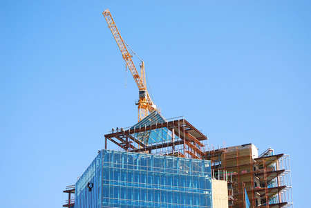 Building construction with crane and people on roof working Stock Photo