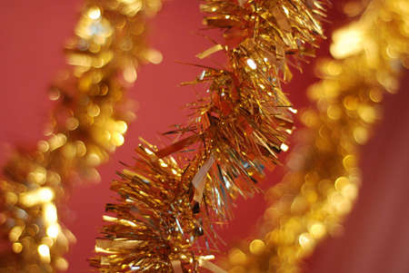 Bright Christmas golden garland on red background with shallow DOF Stock Photo