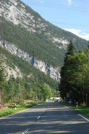 Highway in Austrian Alps with mountain and pines beside the road Stock Photo