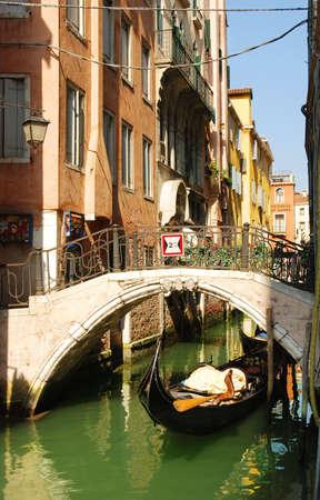 Gondola under bridge in venetian canal Stock Photo