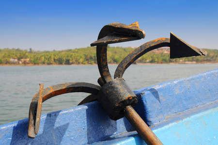 Rusty iron anchor on board a ship in open sea
