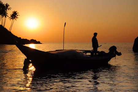 Silhouette of fisherman with nets in the sea on his boat at the dusk. Palm trees on the hill on background Stock Photo