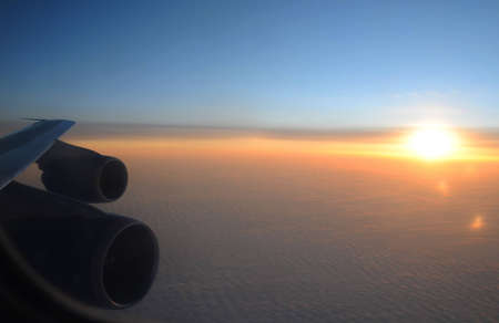 Sunset clouds from the plane with the detail of plane wing, fuselage and engines Stock Photo