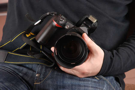 Professional photographer sitting and holding photo camera (digital SLR) in hands closeup