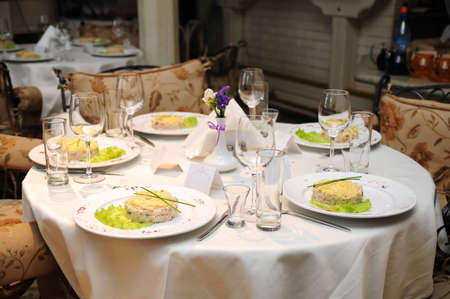 Wedding table with decoration in fine restaurant with food served in plates