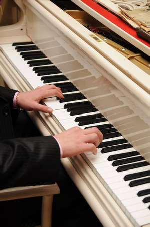Mans hands playing piano