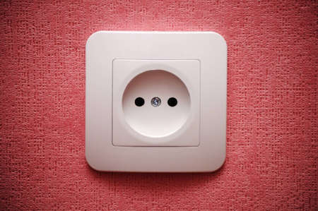 Electric plug connector (outlet) on red wall Stock Photo