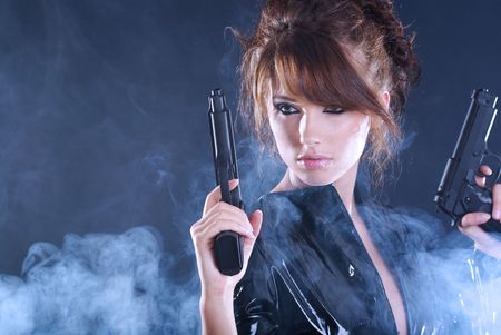 Sexy woman holding gun with smoke photo