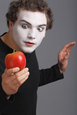 Portrait of Mime with red apple on grey background photo