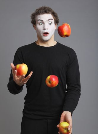 par: Portrait of Mime with red apple on grey background