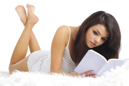 lying on bed: A young attractive woman lying on the bed with a book  Stock Photo