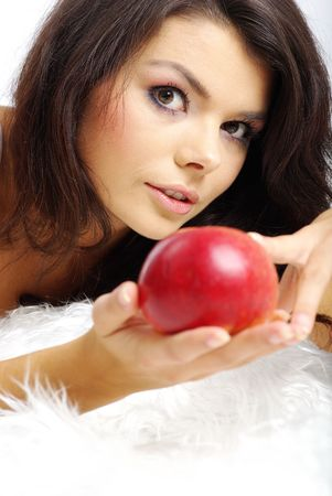 Portrait of  woman sitting on bed and eating fresh red apple photo