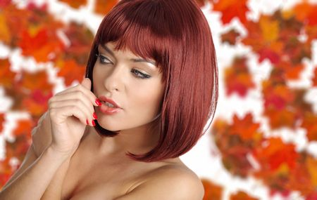 Beautiful young woman with red hair amd maple leaves photo