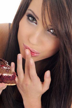 Girl eating piece of cake. Isolated. photo