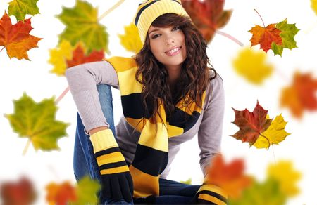 Beautiful girl wearing hat and gloves and maple leaves photo