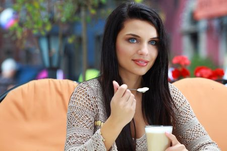 Young woman drinking tea in a cafe outdoors  photo
