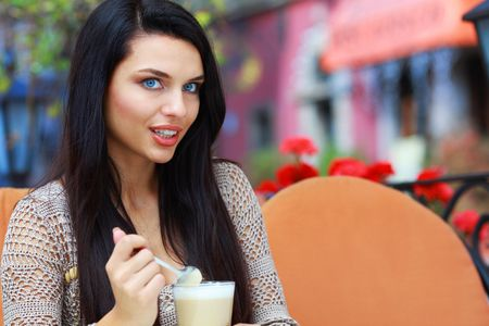 Young woman drinking tea in a cafe outdoors  Stock Photo