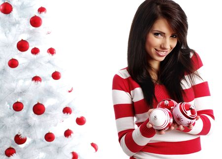 Young Woman decorating white christmas tree photo
